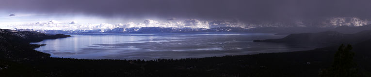 Lake Tahoe panoramic. Panoramic view of storm clouds over Lake Tahoe with snow covered Sierra Nevada mountains in background, California and Nevada, U.S.A stock image