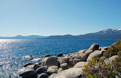 Lake Tahoe shore with stones and snow mountains Royalty Free Stock Photos