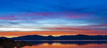 Lake Tahoe Sunset Sky. Sunset at Sand Harbor, Lake Tahoe, Nevada.  Large granite boulders reflecting into glassy water with warm light Royalty Free Stock Photos