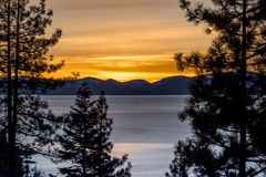 Lake Tahoe at sunset. Sun setting over Lake Tahoe in the winter with tress in the foreground Stock Photo