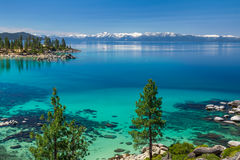 Lake Tahoe. Turquoise waters of Lake Tahoe with view on snowy peaks of Sierra Nevada mountains stock photo