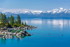 Lake Tahoe. Turquoise waters of Lake Tahoe with view on snowy peaks of Sierra Nevada mountains royalty free stock photos