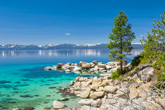 Lake Tahoe. Turquoise waters of Lake Tahoe with view on snowy peaks of Sierra Nevada mountains royalty free stock image