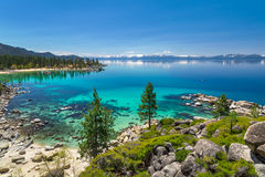 Lake Tahoe. Turquoise waters of Lake Tahoe with view on snowy peaks of Sierra Nevada mountains stock image