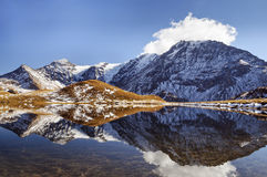 Lake in Tarentaise. A blue lake reflecting the snowy mountain in Savoie Stock Photo
