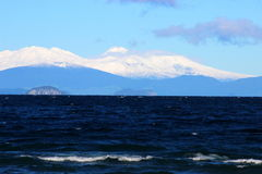Lake Taupo and Tongariro National Park. Biggest New Zealand�s lake Taupo and snowy mountains in the background Royalty Free Stock Images