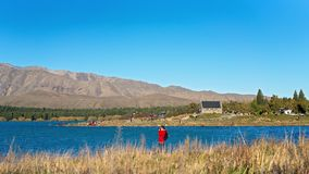 TOURISTS STANDING ON SHORE OF LAKE TEKAPO PHOTOGRAPHING THE CHURCH OF THE GOOD SHEPHERD, NEW ZEALAND stock photos