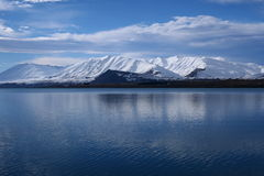 Lake Tekapo in Winter. The spectacular view of Lake Tekapo, New Zealand, in winter with the snow mountain backdrop stock photo