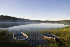 Lake Tevsjon near Ljusnedal. Moored boats in Lake Tevsjon near the Swedish village Ljusnedal early in the morning Stock Image