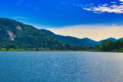 Lake in Thailand with blue sky and mountains in the background stock photography