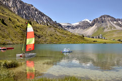 Lake of Tignes in France. Lake of Tignes with sailboat and pedalo and Tignes-Val Claret village in the background. Tignes is a commune in the Tarentaise Valley Stock Photos