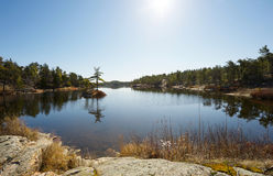 Lake with tiny islet in Spring. Wide angle image of a beautiful lake in the early Spring with a tiny islet with three weathered trees in Northern Ontario stock photos