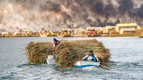 Woman in a boat carrying reed on the Titicaca lake in Bolivia. Lake Titicaca, Bolivia - September 2017: Woman in a boat carrying reed on the Titicaca lake in Royalty Free Stock Image
