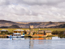 Lake Titicaca, 6/13/13, man with boat waiting in village. Men with traditional & modern boats in Reed Islands, Peru on Lake Titicaca Stock Photos