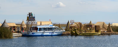 Lake TIticaca tourist boat and totora boat at reed island royalty free stock photo