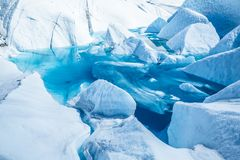 Lake on top of the Matanuska Glacier in Alaska. The deep blue water has flooded an old ice cave or moulin on the surface. Blue glacier lake of melting ice of the stock image