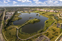 Lake, Townhomes and Community Center Aerial. Aerial view of a lake and peninsula near a community center and townhomes with walking paths and bridge in The Glen Stock Photos