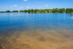 Lake and Trees. Clear blue lake - bright day - few clouds Stock Image