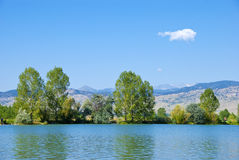 Lake, Trees, Mountains and Wispy Cloud Stock Images
