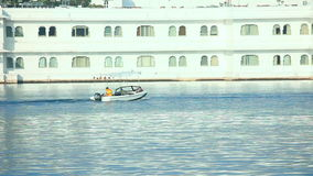 Lake in Udaipur. Boat passing allong the lake palace near Udaipur, India stock footage