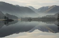 Lake Ullswater reflections. Reflections in lake Ullswater with early morning mist resting in the valleys at the foot of the mountains behind stock photo
