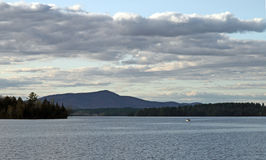 Lake umbagog landscape with small boat in distance.  New Hampshi Stock Images