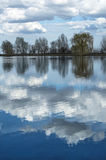 Lake under blue cloudy sky Royalty Free Stock Image