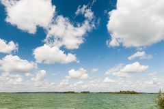 Lake under  blue sky with clouds Royalty Free Stock Image