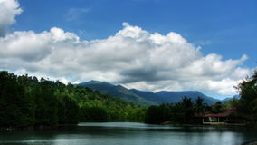 Lake under clouds time lapse. Lake surrounded by trees and racing clouds time lapse stock footage