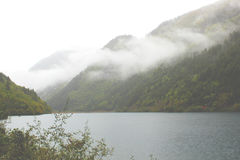 Lake under foggy mountains Royalty Free Stock Image
