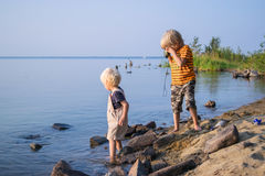 Two brothers kids play near lake with binoculars. Lake Uveldy, the Urals landscape, Russia Royalty Free Stock Photo