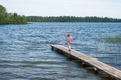 Little girl  walking on the pier at the lake Stock Photo