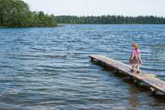 Little girl walking on the pier at the lake. Little girl on the pier at the lake Valdai royalty free stock photos