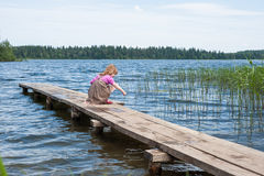 Little girl on the pier at the lake. Valdai stock photos