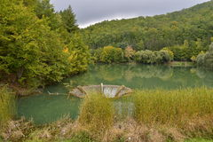 Lake Vida with autumn forest and overflow funnel near Luncasprie. Stock Image