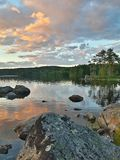 Lake with a view. Beautiful Swedish lake with mountains, an island, trees and rocks. Calm and magical Stock Images