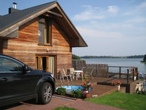 Lake view house with car and swimming pool. Wooden comfortable lake view house with terrace, car and swimming pool royalty free stock image