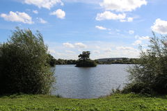 Lake view. Lakeland scenery with a beautiful blue summer sky surrounded by trees and hedges Stock Photo
