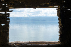 Lake view. With mountain and clouds in background as seen through the window of house made of sticks Royalty Free Stock Image