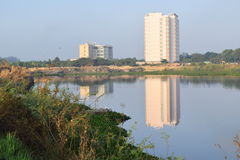 Lake view with some shrubs, rock and building reflect on the water surface Royalty Free Stock Photography