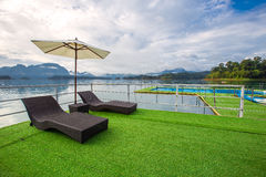 Lake view in summer with relaxation seat and umbrella in wooden terrace at Thailand Summer Season Stock Photos