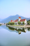 Lake and villa buildings. Villa buildings reflected in lake with mountains in background Stock Photo