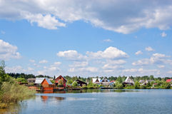 Lake and the village. Lake with the pure water with village ashore. The blue sky with white clouds stock photography