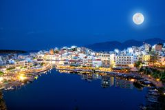 The lake Voulismeni in Agios Nikolaos, Crete, Greece. The lake Voulismeni in Agios Nikolaos at night with fullmoon, a picturesque coastal town with colorful Stock Images