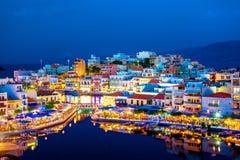 The lake Voulismeni in Agios Nikolaos, Crete, Greece. The lake Voulismeni in Agios Nikolaos at night with fullmoon, a picturesque coastal town with colorful Stock Photo