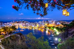 The lake Voulismeni in Agios Nikolaos at night with fullmoon, a picturesque coastal town with colorful buildings around the port. The lake Voulismeni in Agios Stock Photos