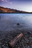 Lake wakatipu rock. A small rock in lake wakatipu with kelvin heights in the background. Taken near queenstown, New Zealand Stock Photos