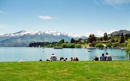 Lake Wanaka, New Zealand. Tourists enjoying a sunny day on the shore of lake Wanaka in the South Island of New Zealand Royalty Free Stock Photo