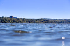 Lake water with houses on background Royalty Free Stock Photography