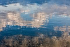 Lake water reflecting the sky. Lake water reflecting blue sky with clouds stock images